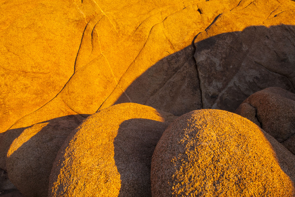 This cluster of round boulders against a larger rocky slope, accented by evening light to highlight the shapes and textures...
