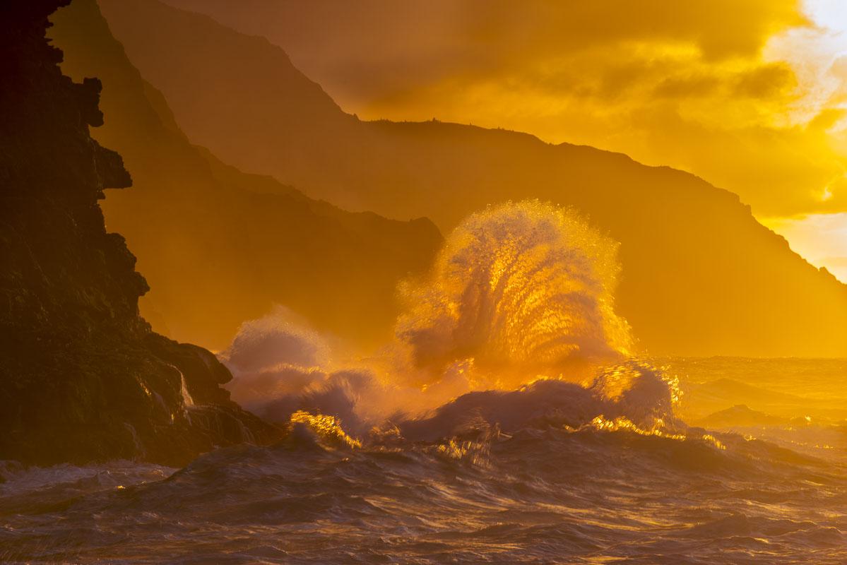 Surf crashes on the Na Pali coast of Kauai at sunset.