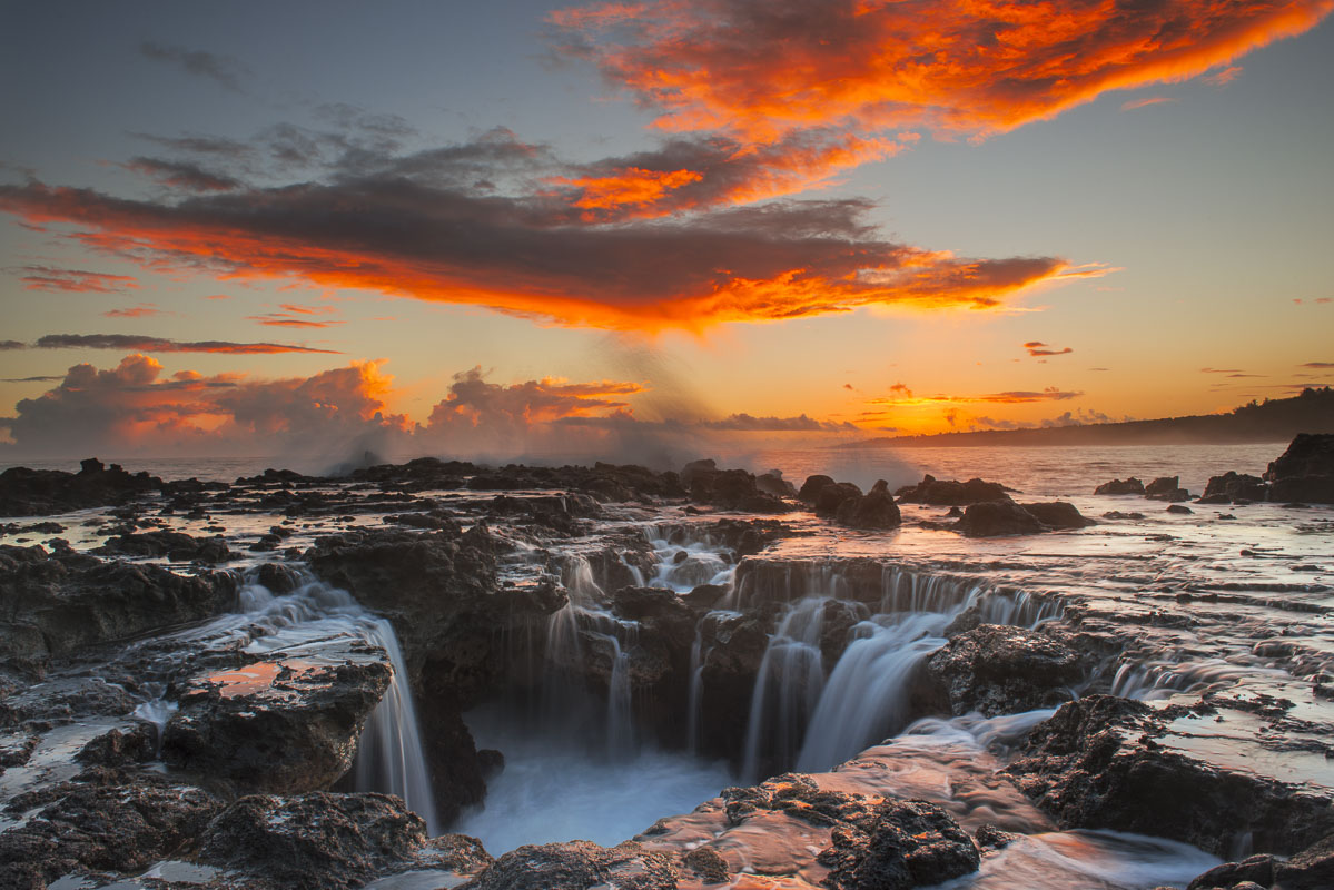 Surf spills into a hole in a rock outrcop at sunrise on the east side of Kauai, Hawaii.