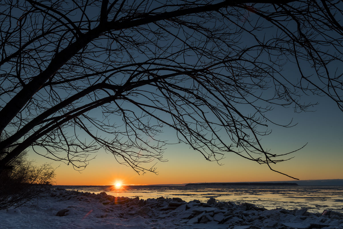 The sun dips below the horizon in a view from the shores below Point Woronzof in Anchorage in winter.