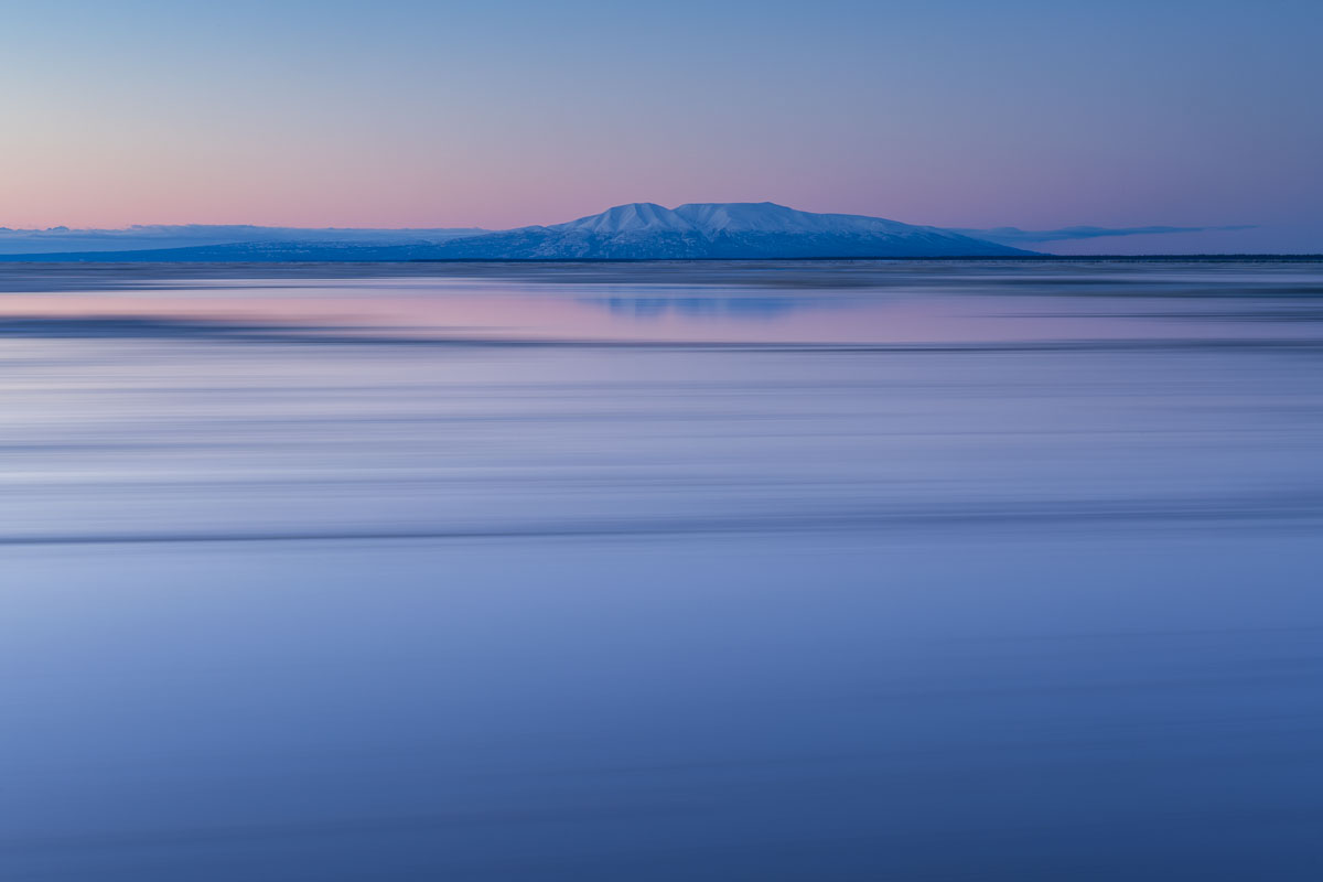 Mt. Susitna looms in the background as the winter tides zoom by in a long exposure at sunset.