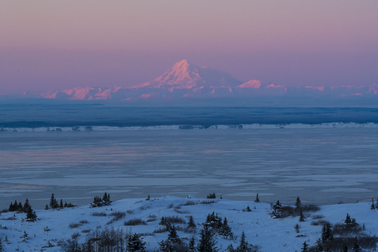 Morning alpenglow lights up Mt. Redoubt, an active stratovolcano in the Aluetian Range, as sunrise lights up the morning in mid...