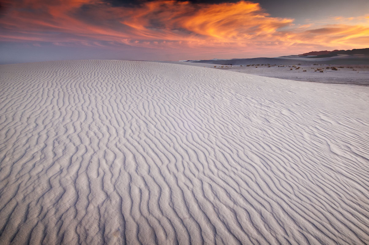 Clouds in the sky light up with the colors of sunset over the gypsum dunes of White Sands National Park, New Mexico.