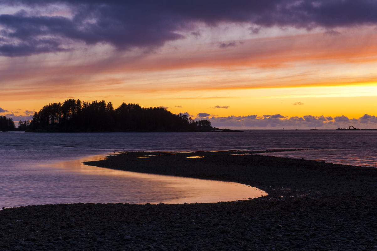 The sun sets in mid-February at Crescent Harbor, with the low tide exposing the shoreline along the Sitka National Historic Park...