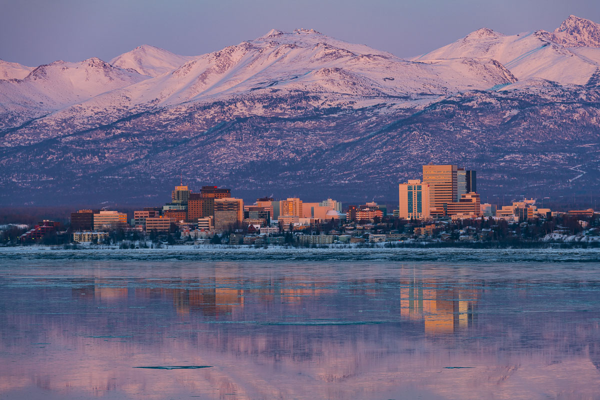 The last post-sunset glow adds warming light to the Anchorage downtown skyline and Chugach Mountains in late winter.