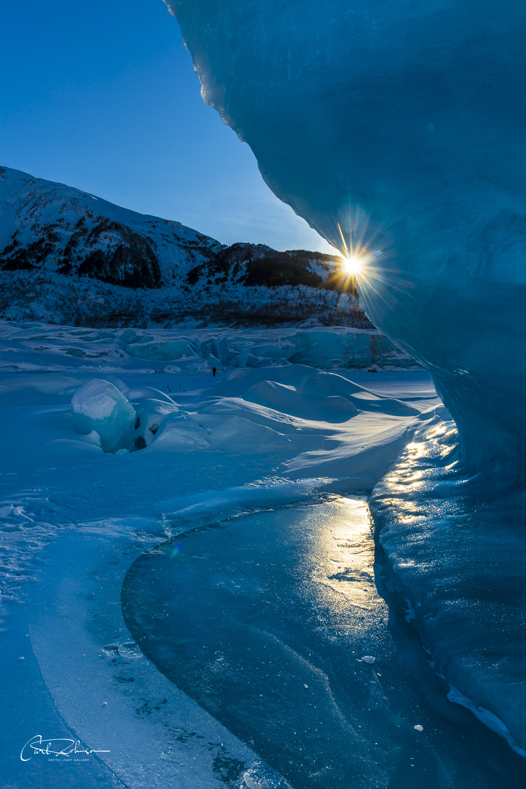 The late afternoon sun peeks from behind a large iceberg suspended in the frozen lake at Spencer Glacier.