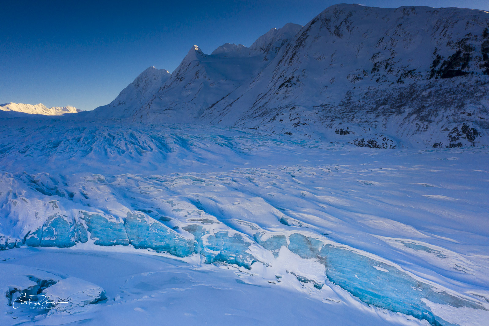 The toe, or edge, of the Spencer Glacier turns a deep blue in the shade as the sun drops low on the horizon.