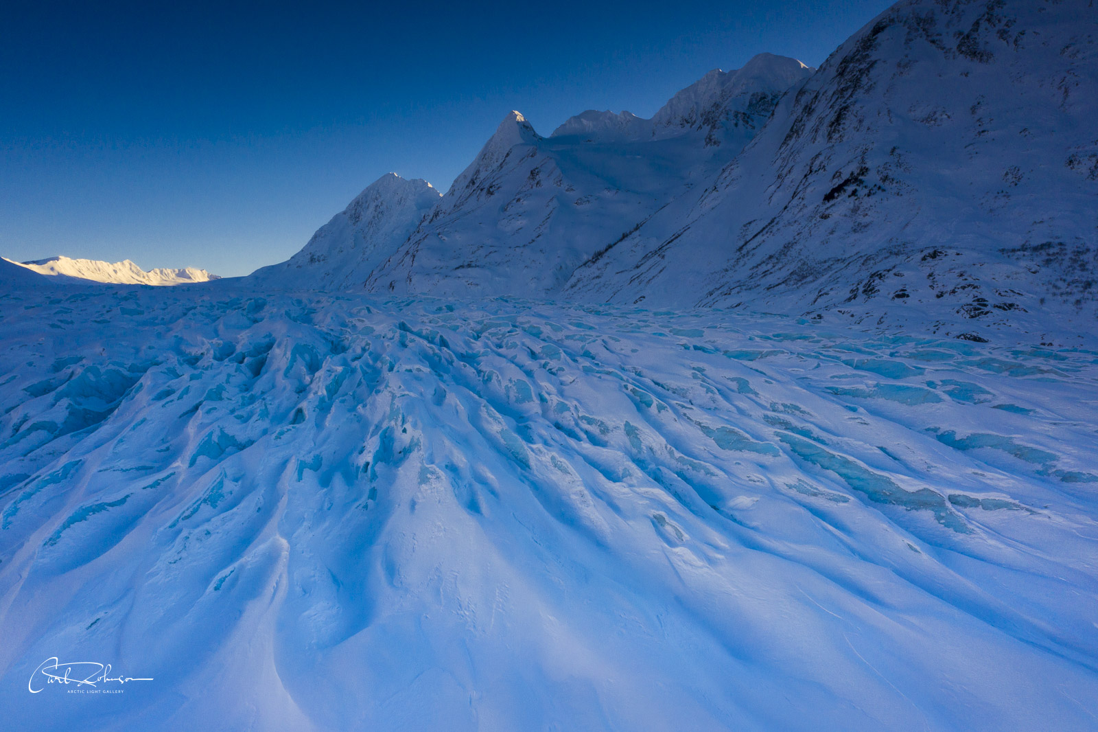 The Spencer Glacier takes on a deep, blue hue in the shade as the day's light drops low on the horizon.