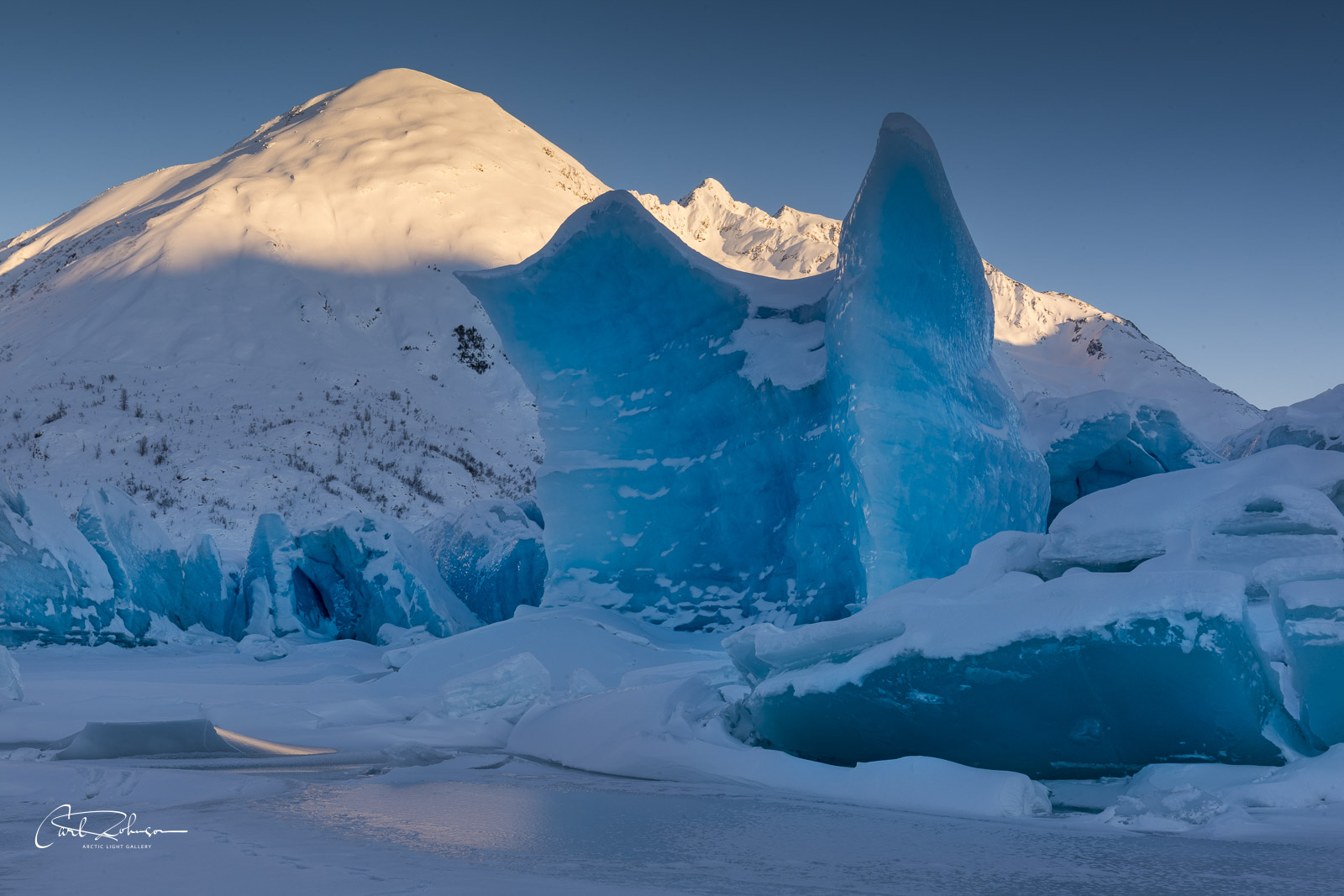 Icebergs and the toe of the Spencer Glacier display deep blue hues in the shadow as the last light of the day's sun shines on...