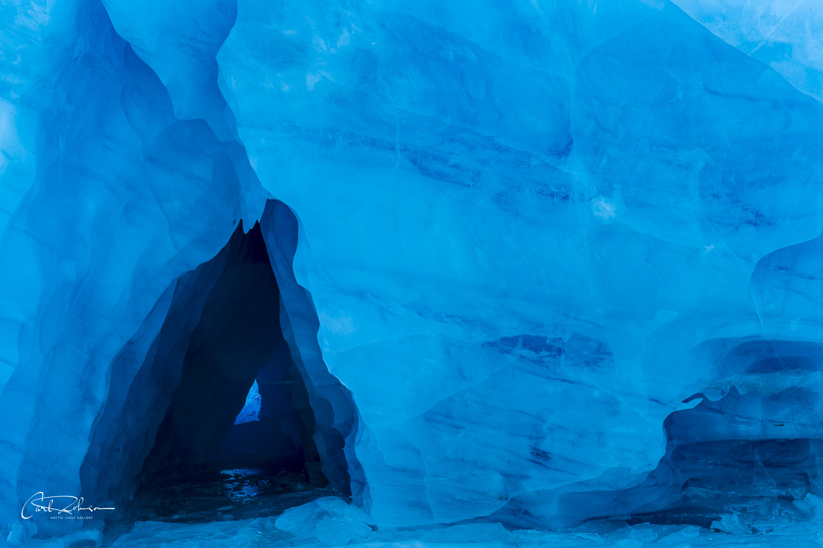 An ice cave in the Spencer Glacier forms a triangle, with deep hues of blue showing in the shade.