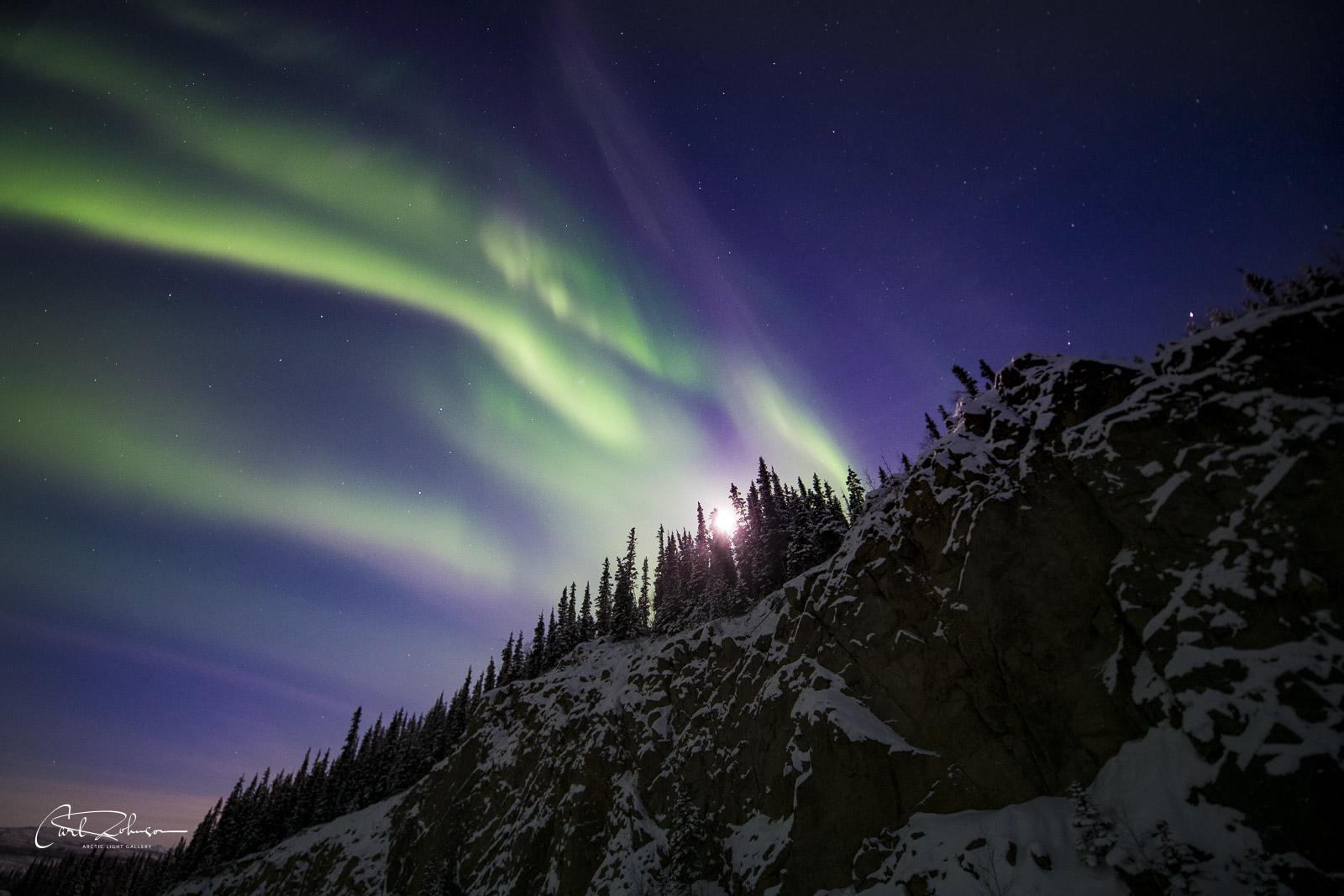 The aurora borealis and moon seem to climb up over a rocky hillside along the Dalton Highway.