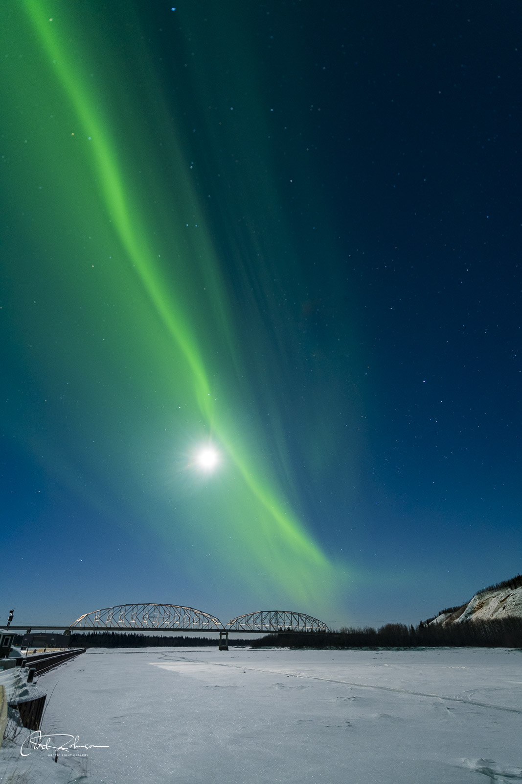The aurora borealis towers over the bridge crossing the Tanana River at the Athabascan community of Nenana.