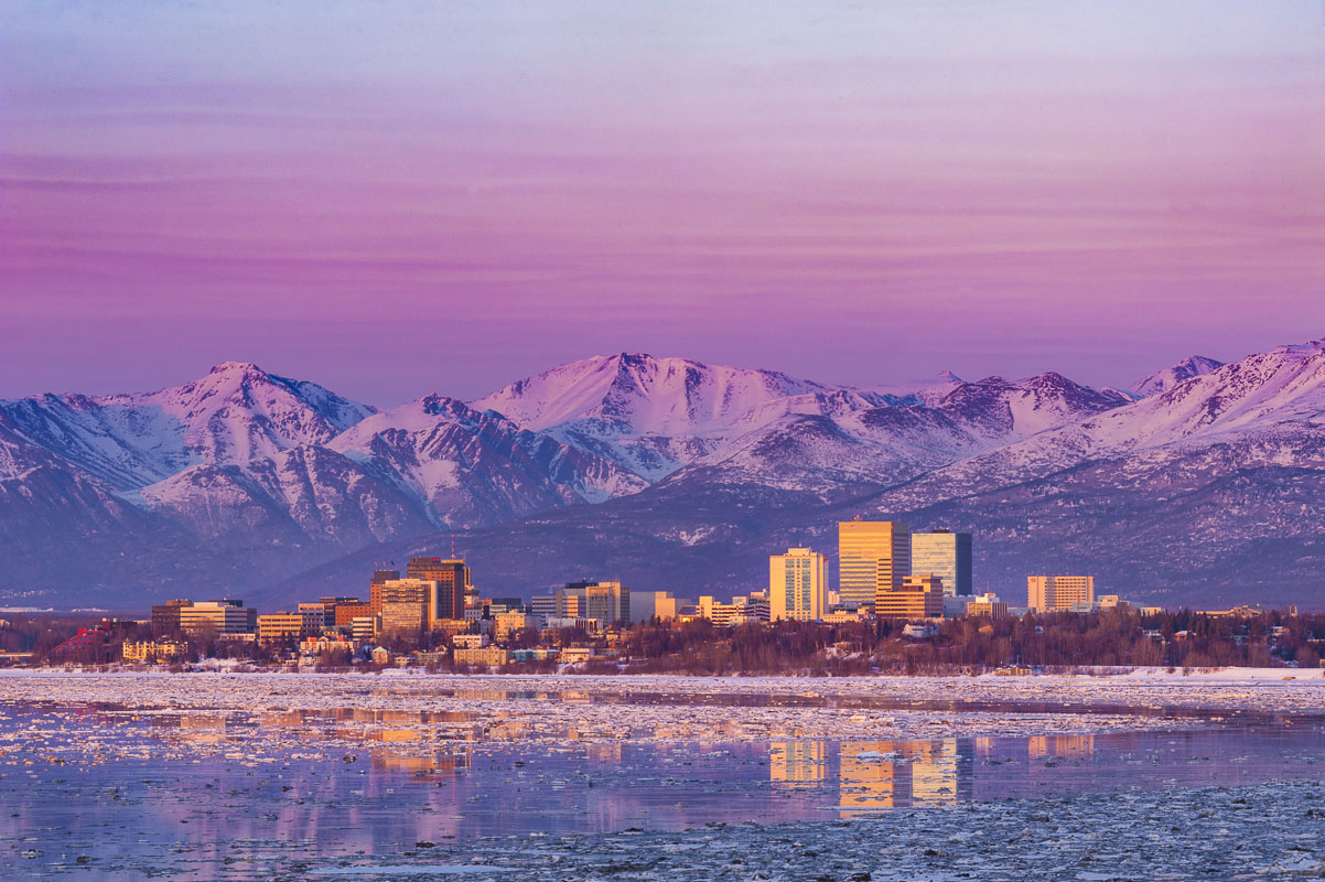 Pink pastels and alpenglow on the snowy mountains fill the scene as the last vestiges of muted sunset glow on buildings in the...