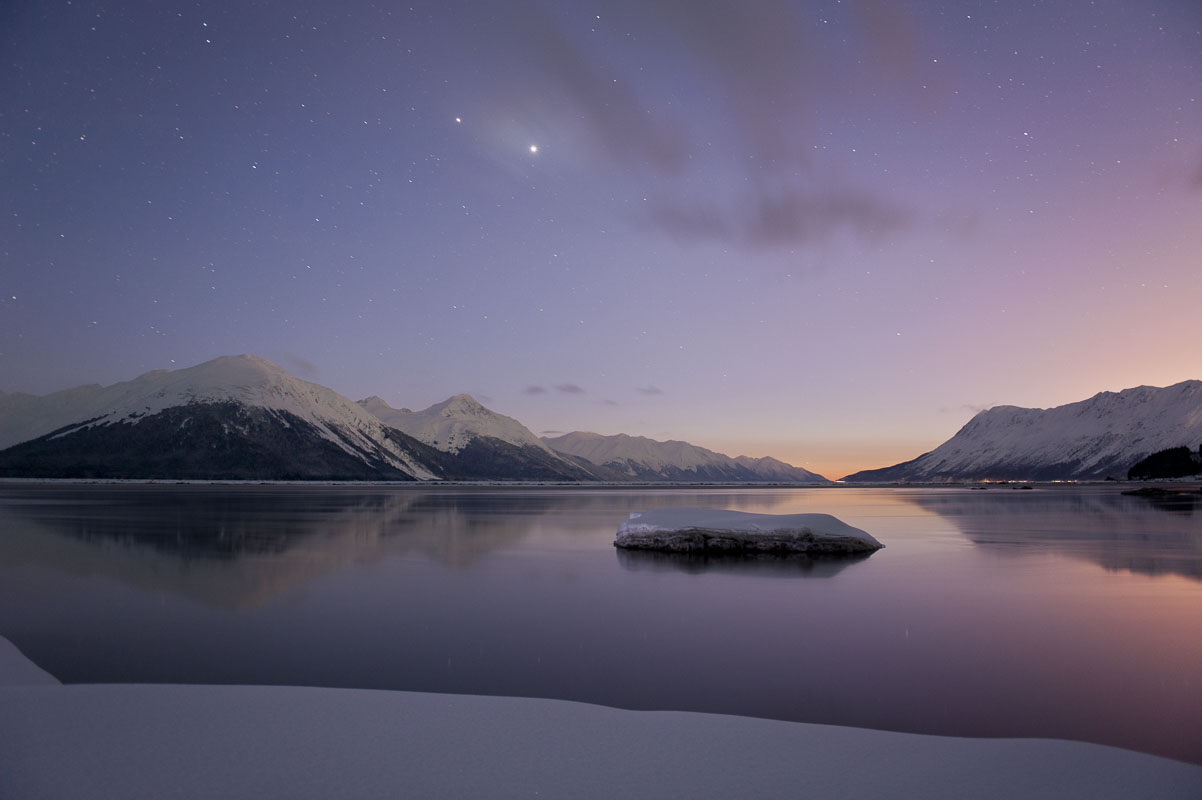 Venus and Jupiter shine brightly in the sky to the west as twilight settles over the calm waters of Turnagain Arm.