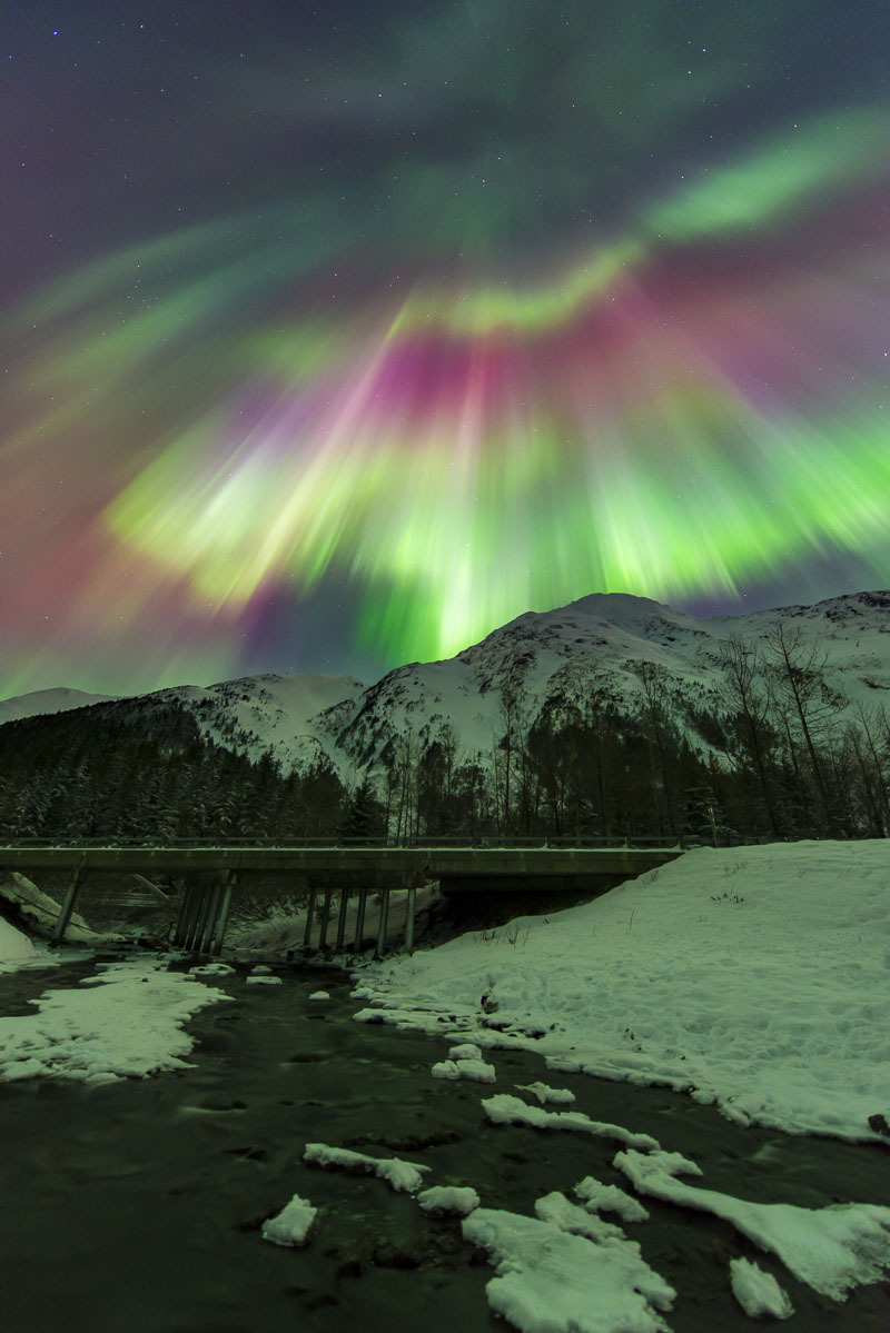 A colorful corona aurora borealis fills the sky over a bridge over a creek in Portage Valley, Chugach National Forest.