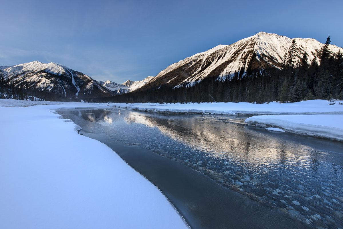 Morning light reflects on ice and open water in the Kootenay National Park, Alberta, Canada.