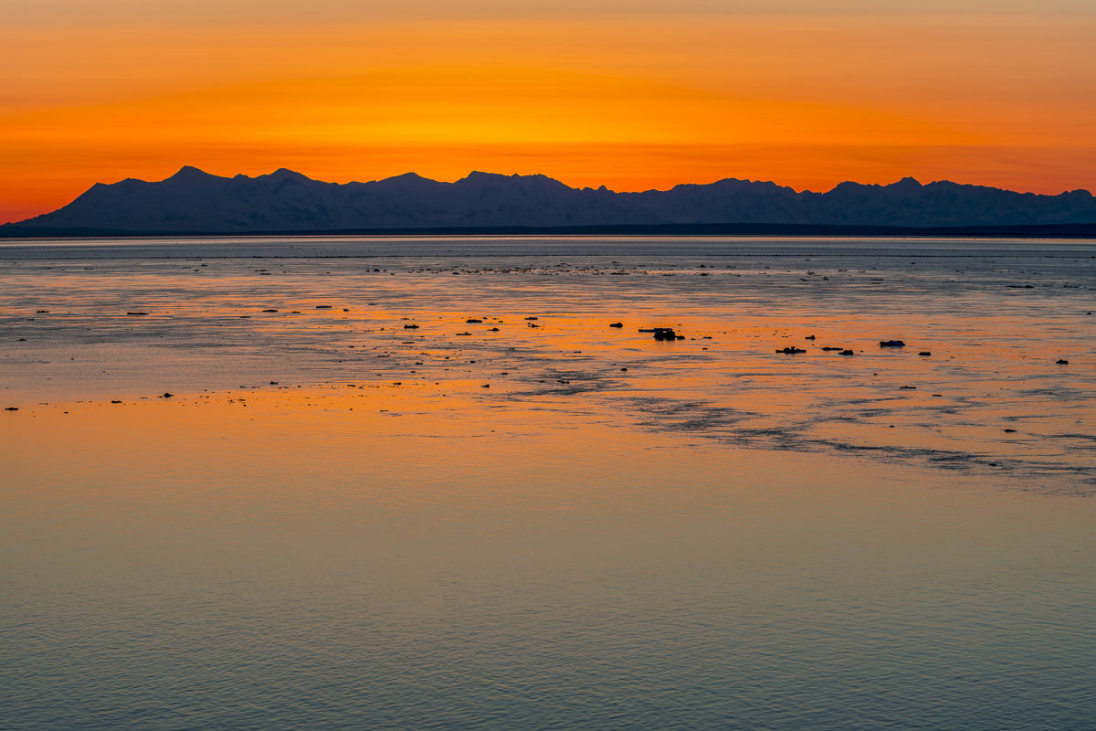 The sky glows gold as the sun sets behing the Tordrillo Mountains on the western side of Cook Inlet. The Tordrillo Mountains...