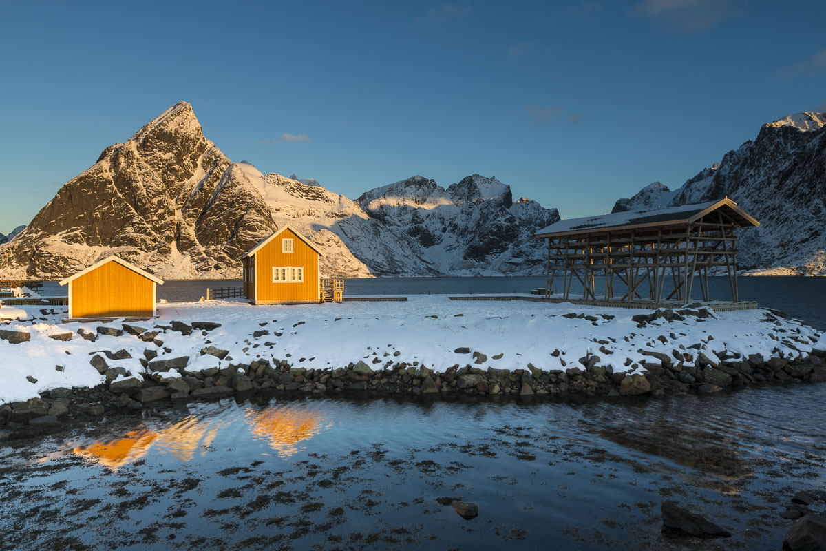 Cabin and fish racks near Reine, Norway, in morning light.