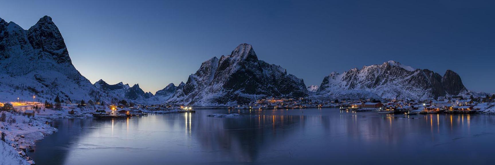 Village lights create pops of warm light as twilight descends upon the village of Reine in the Lofoten Islands, Norway.