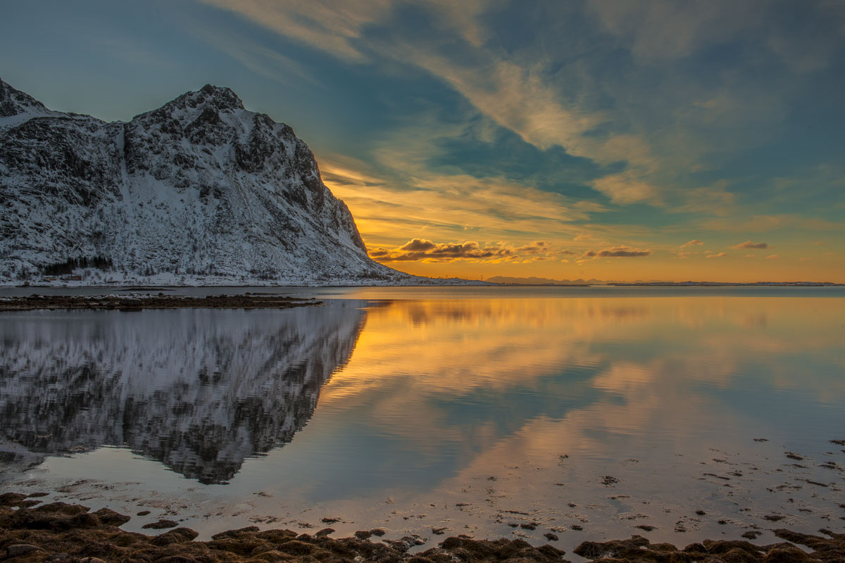 Calm waters in a bay provide reflection of sunrise along a southen coast of the Lofoten Islands.