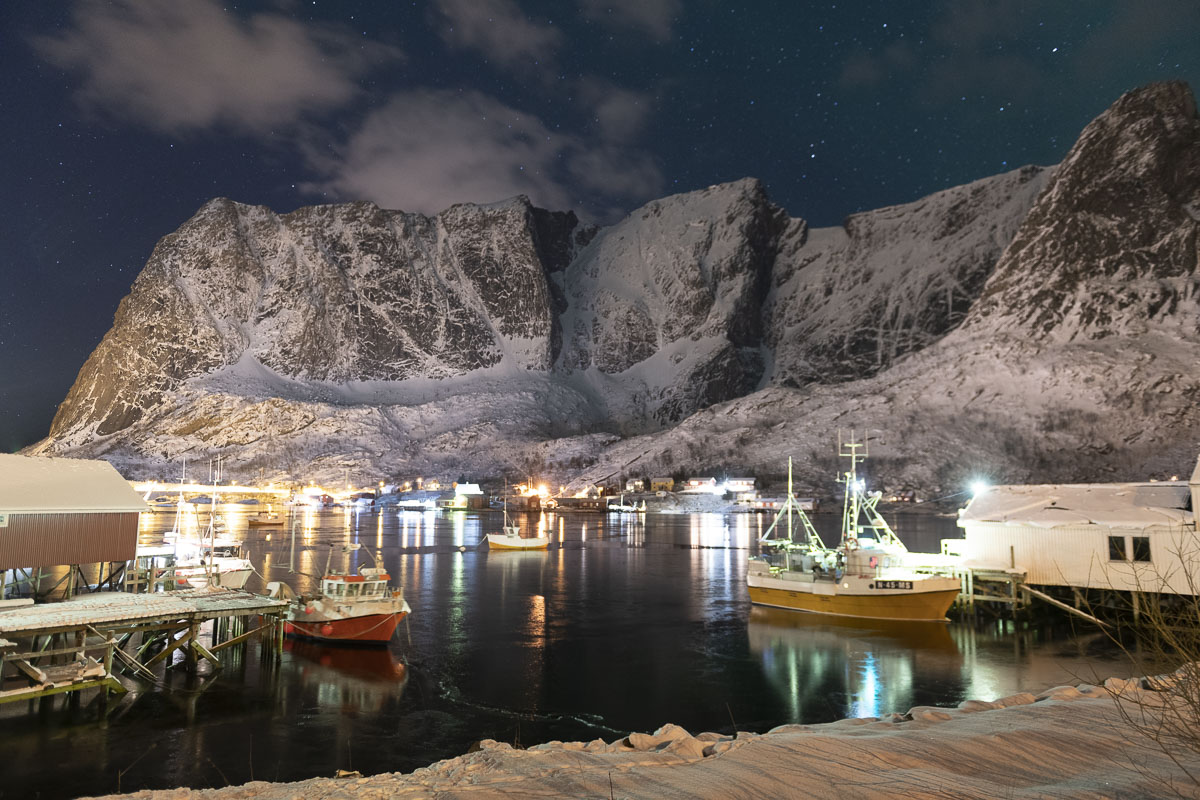 Boats and buildings cast a glow that reflects off Reinebringen in the Lofoten village of Reine.