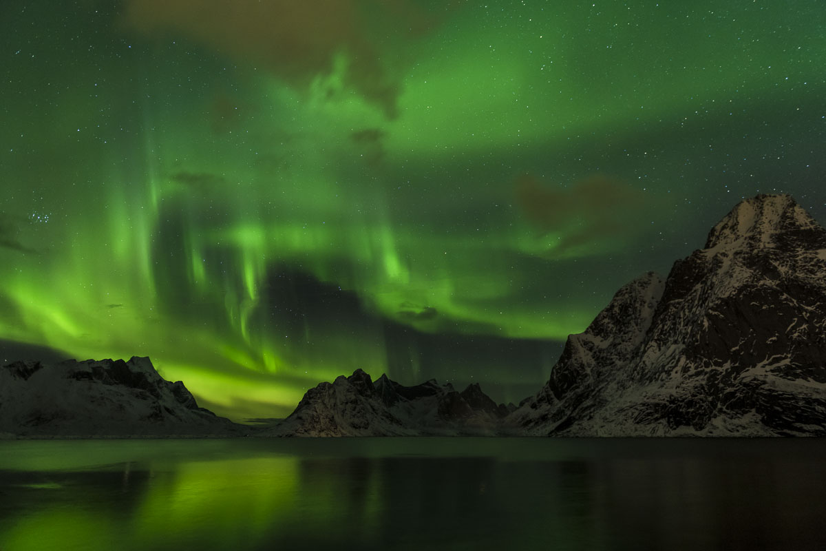 A green aurora borealis fills the sky over a lake in the Lofoten Islands, Norway.
