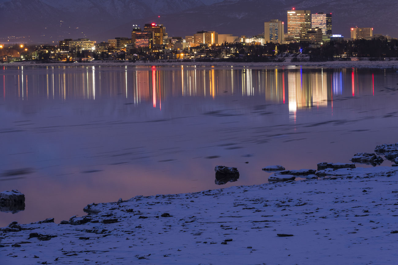 The City Center of Anchorage, Alaska, reflects on the waters of Cook Inlet as movement of high tide carries pieces of sea ice...