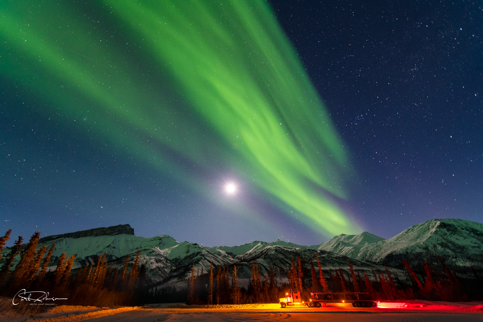 A long haul truck rests at a material site off the Dalton Highway in the Brooks Range as the aurora borealis soars in the sky...