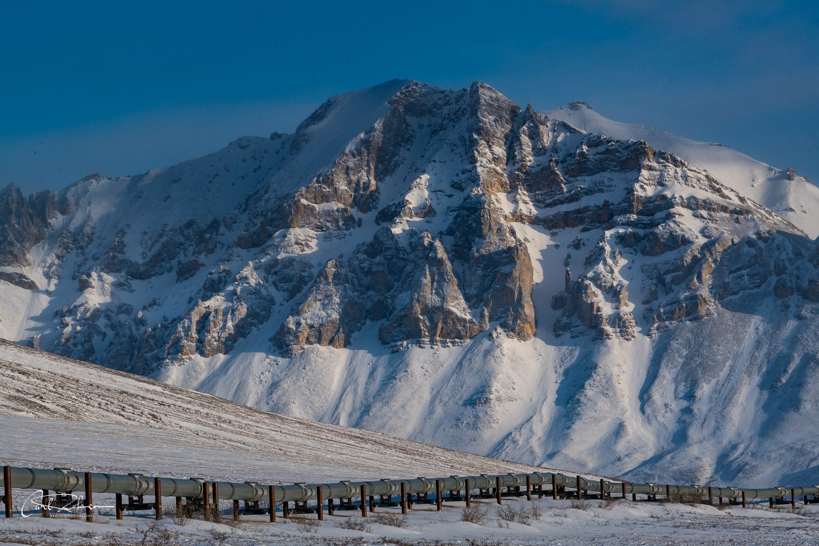 Afternoon light brushes an unnamed mountain in the Brooks Range as the Trans Alaska Pipeline makes its way across the Arctic...