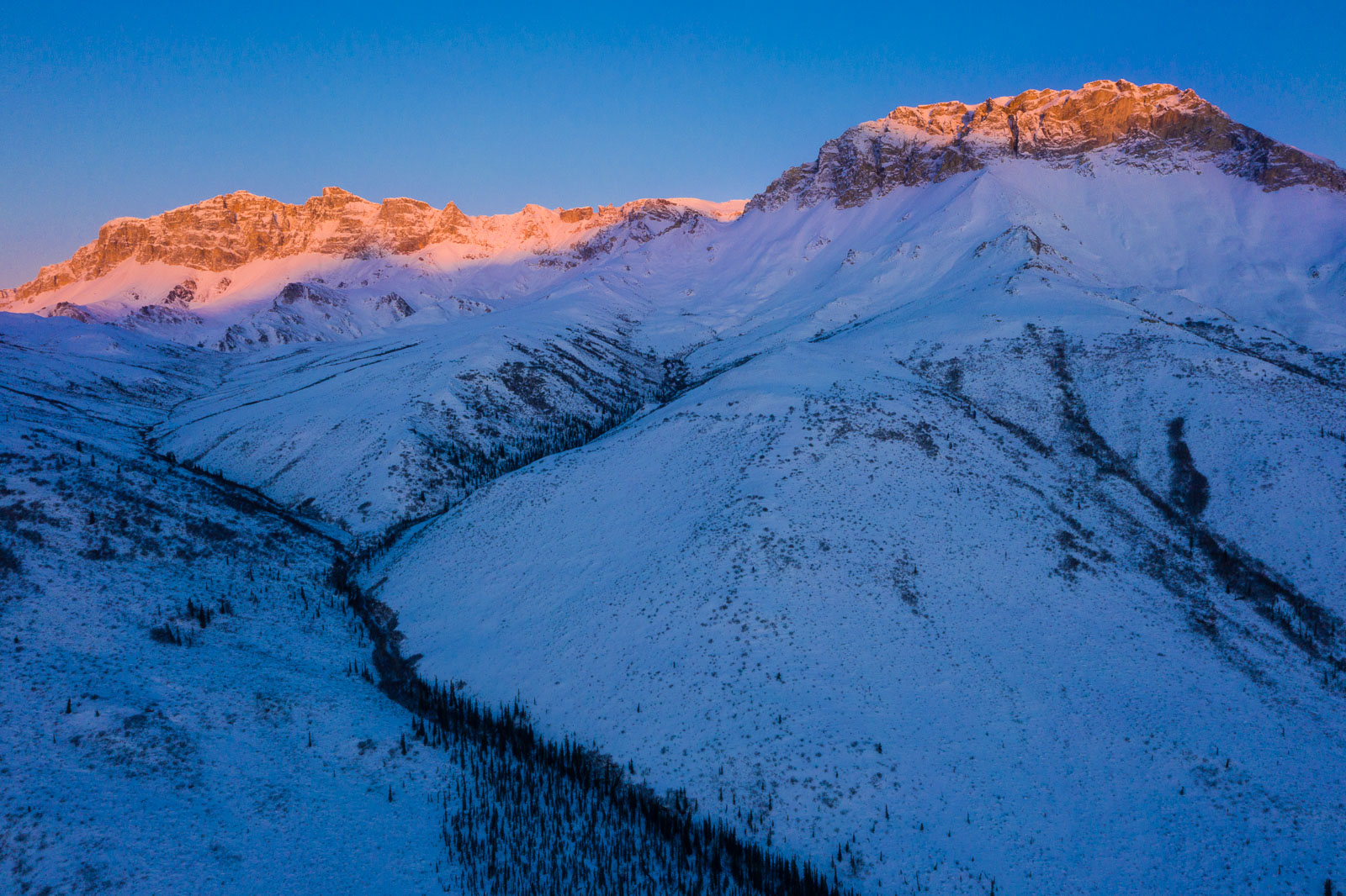 The last rays of evening light turn a mountain ridge pink with alpenglow in the Brooks Range.