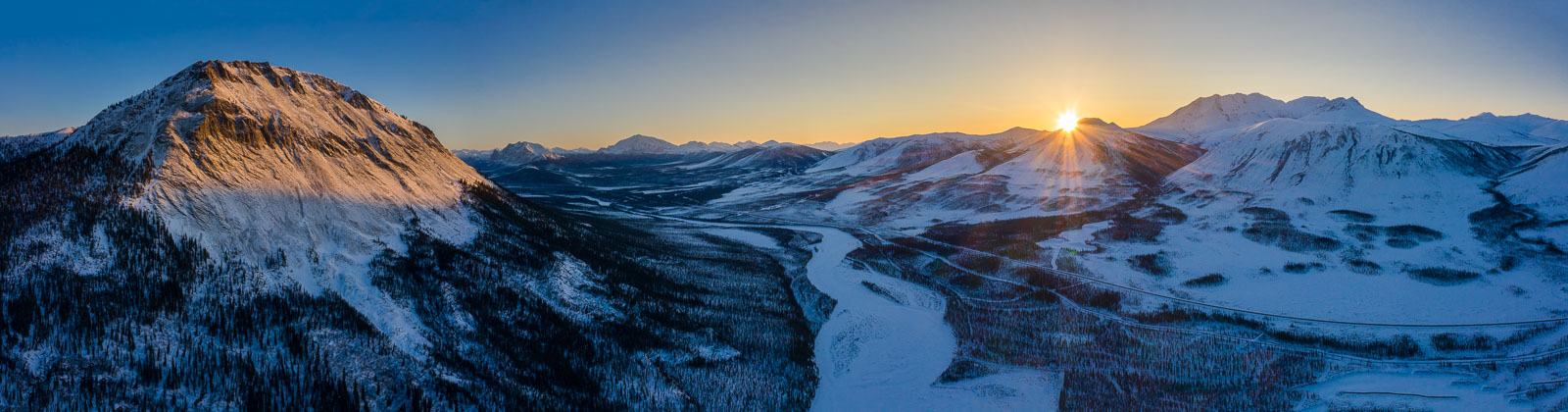The first rays of the sun reach above the mountains to shine above the Middle Fork of the Koyukuk River, the Dalton Highway and...