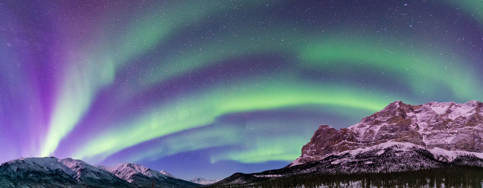 A seven-image stitch panoramic image of the aurora borealis spans across the Middle Fork Koyukuk River valley, with Mt. Sukakpak...