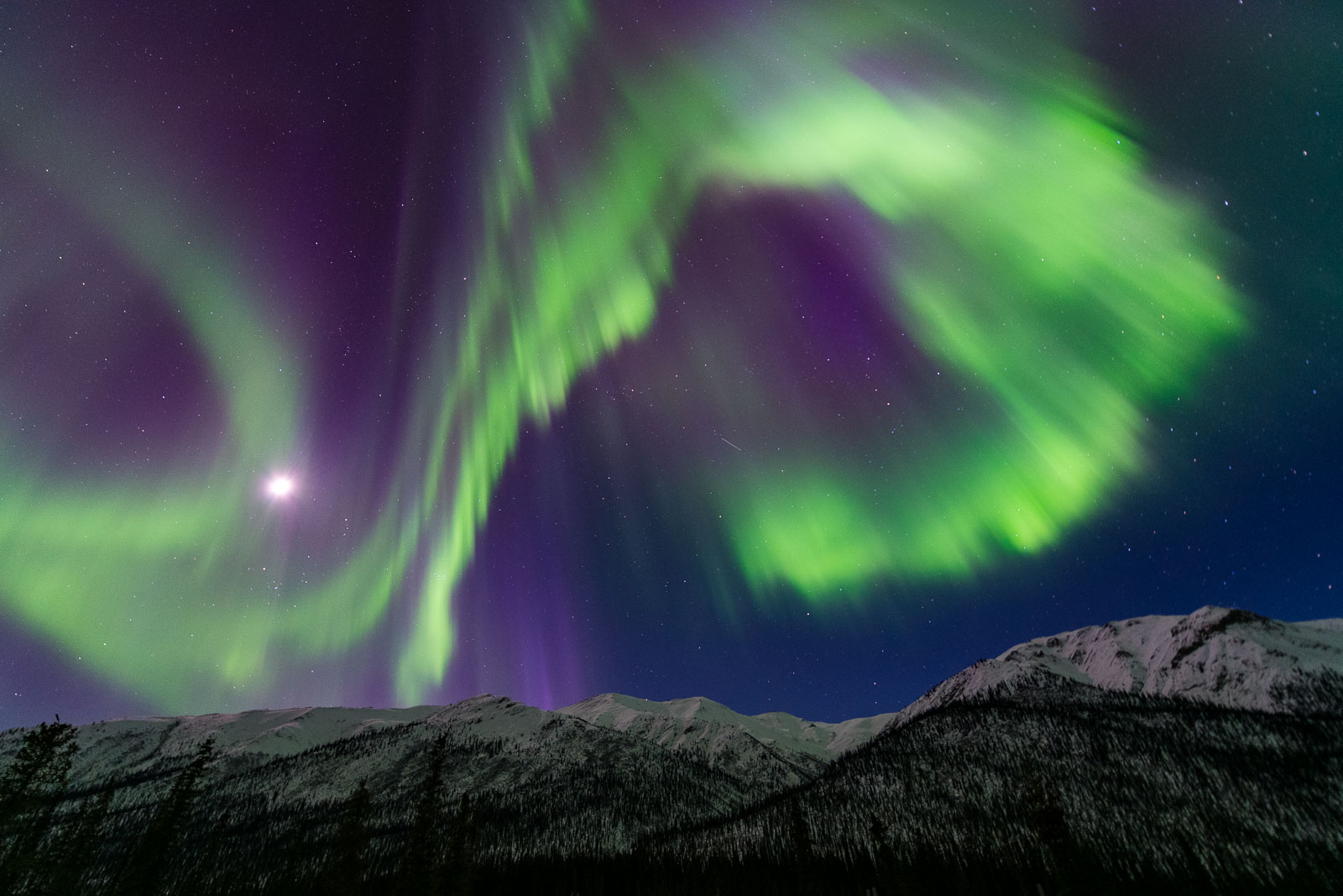 A large, curling arc of the aurora borealis towers over a mountain ridge in the Brooks Range of Alaska.