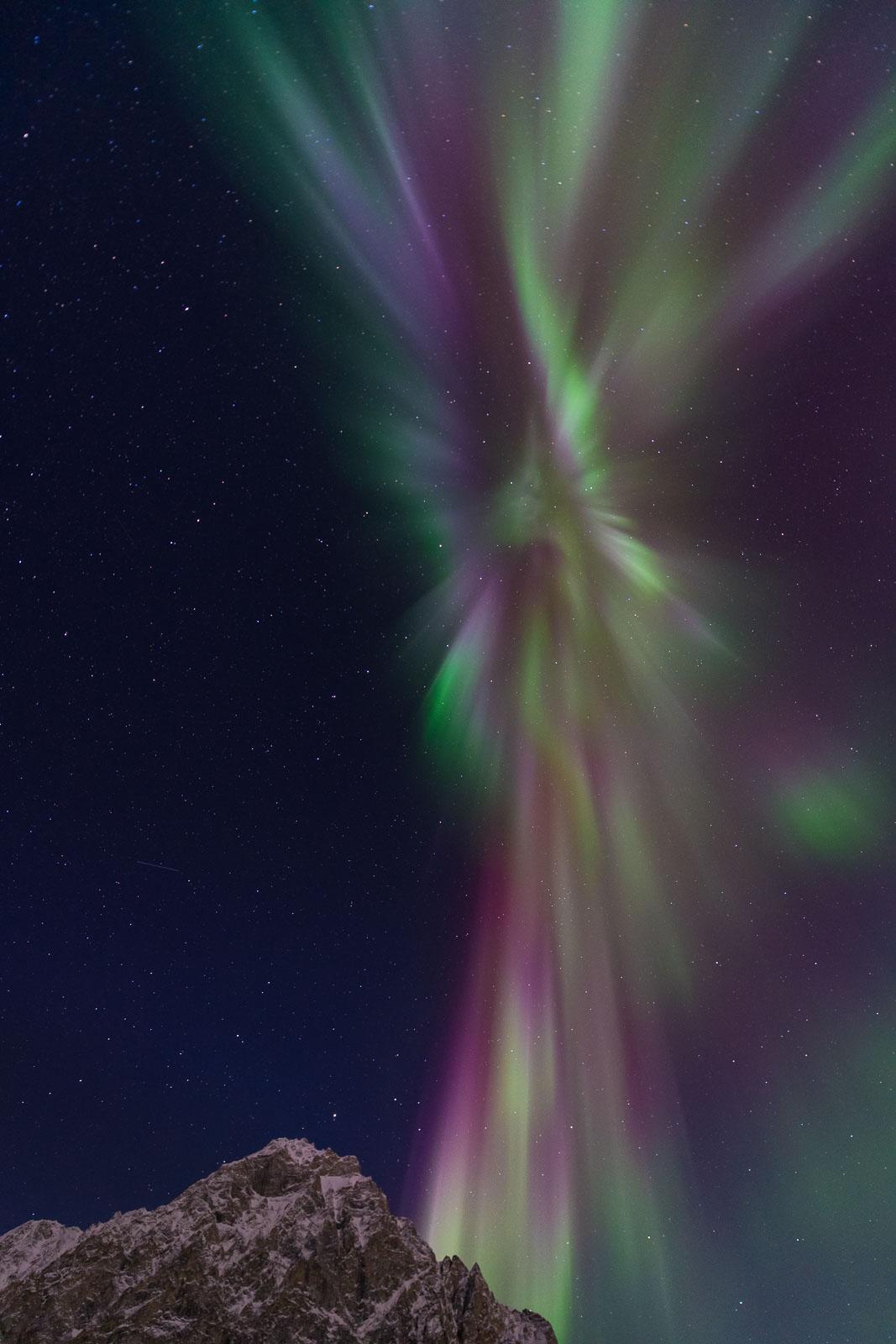 A mixture of purple, red, green and yellow corona display towers over Mt. Dillon, Brooks Range, Alaska.