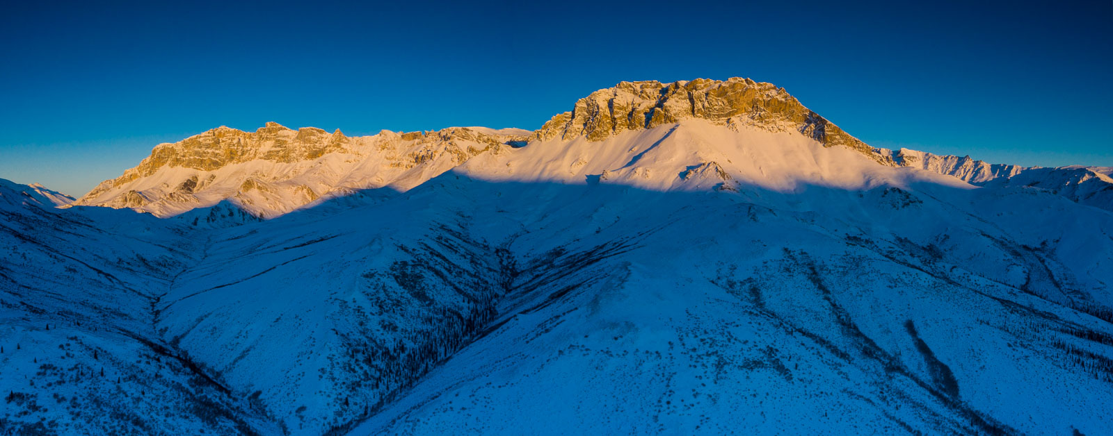 A mountain ridge rises obove the shadow line from mountains to the ast as the sun goes down on the Brooks Range, Alaska.