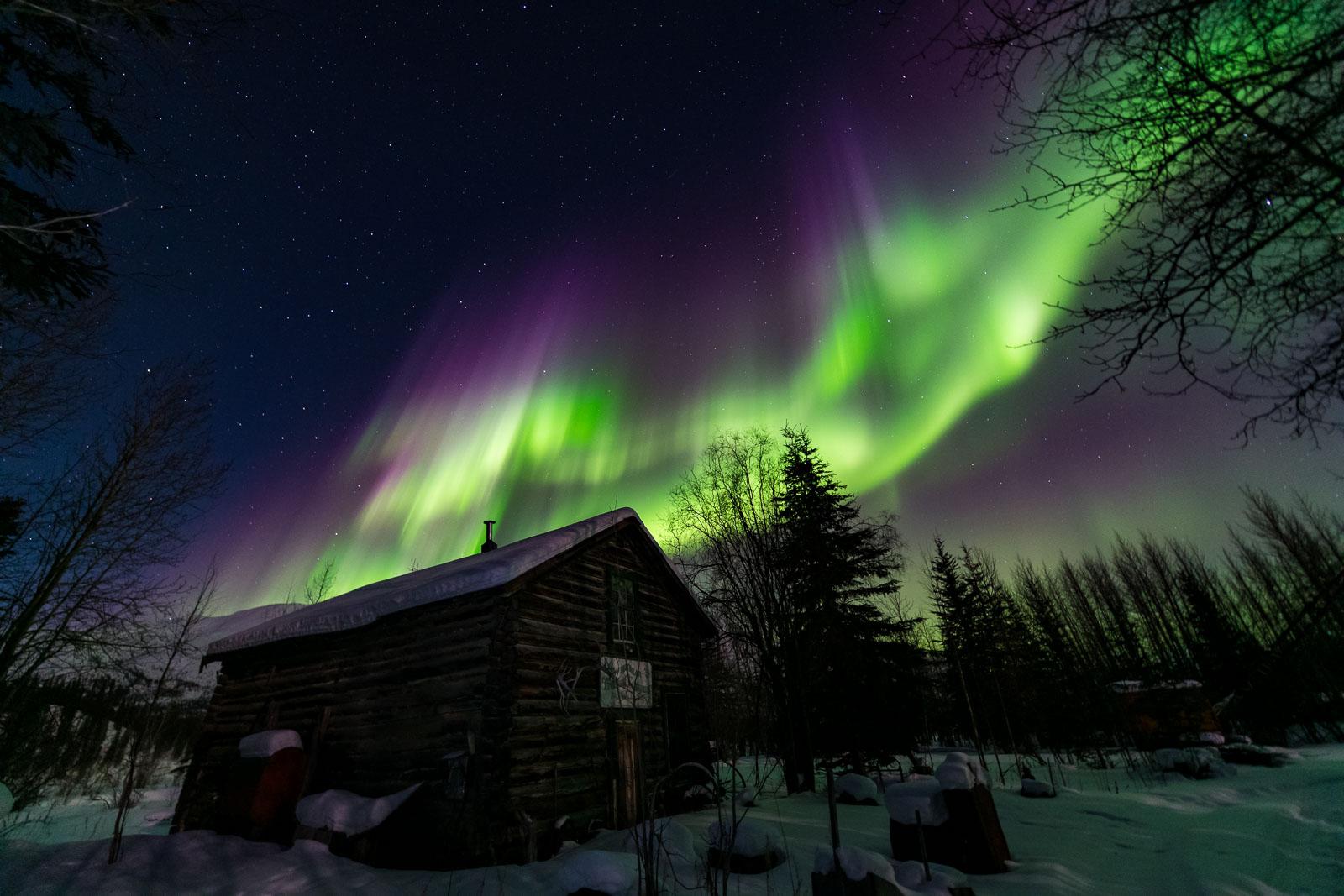 The aurora borealis soars over the historic General Store in Wiseman, Alaska.