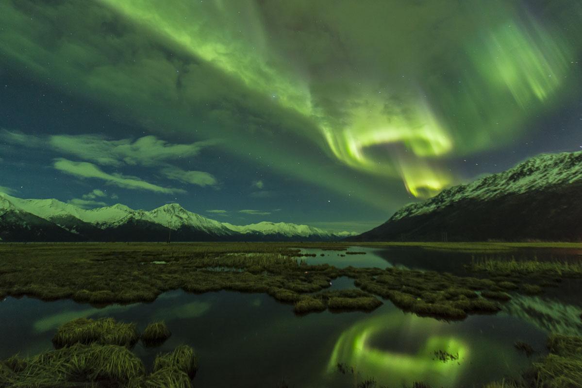 A spring aurora borealis erupts over ponds near Girdwood and Turnagain Arm.