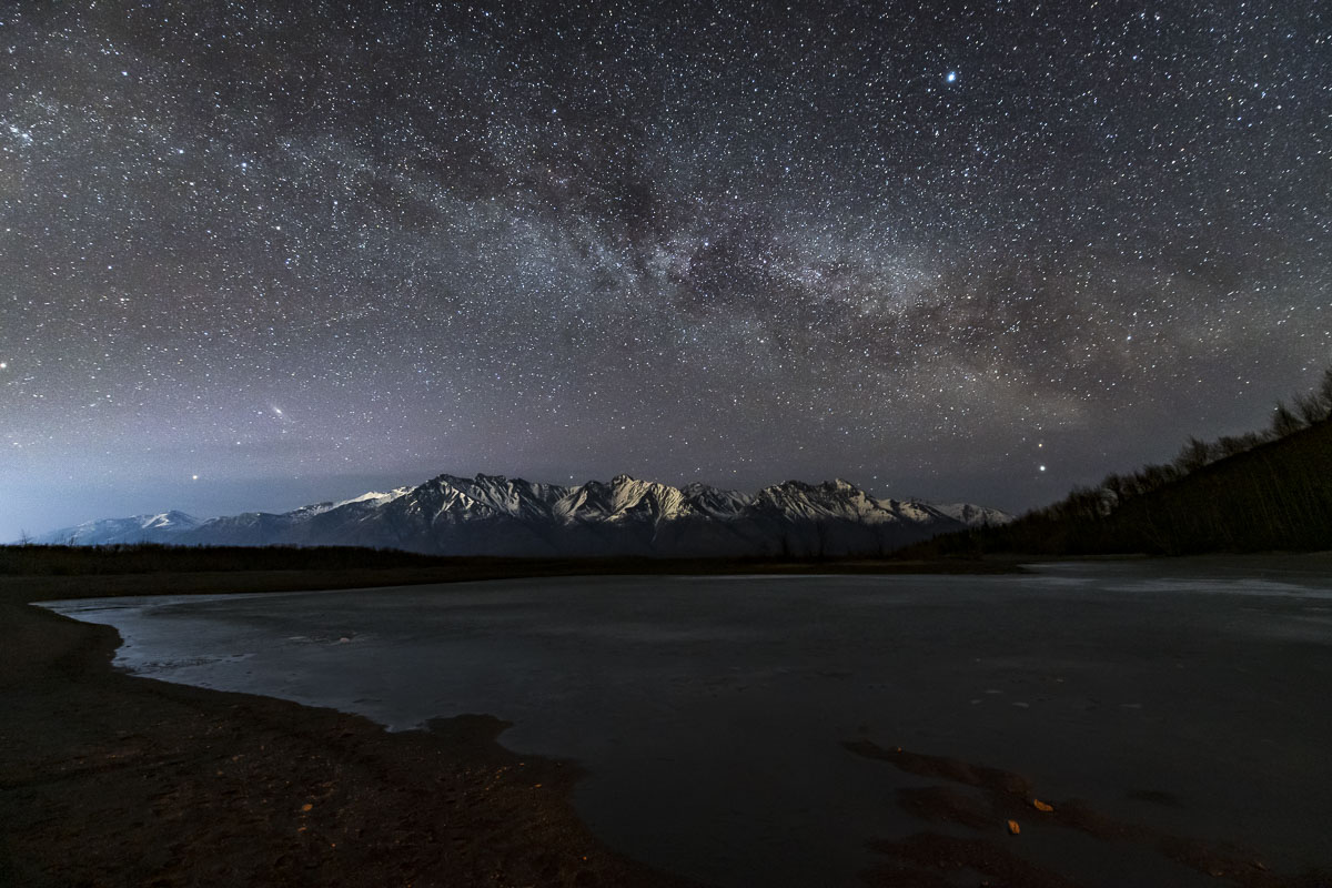 The Milky Way fills the sky over the Chugach Mountains and a frozen Knik River.