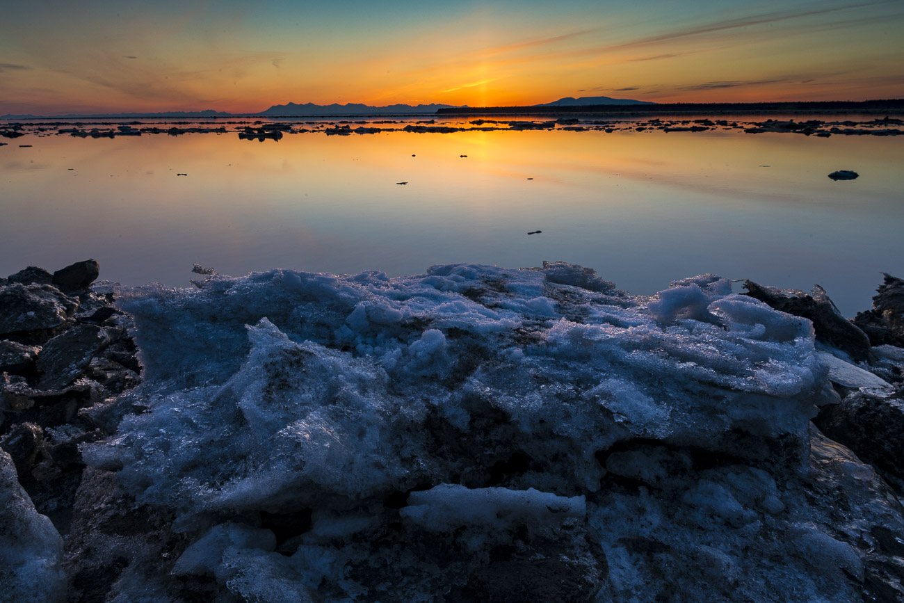 Ice plates from the last high tide pile up along the shores of Cook Inlet as the sun sets in spring.