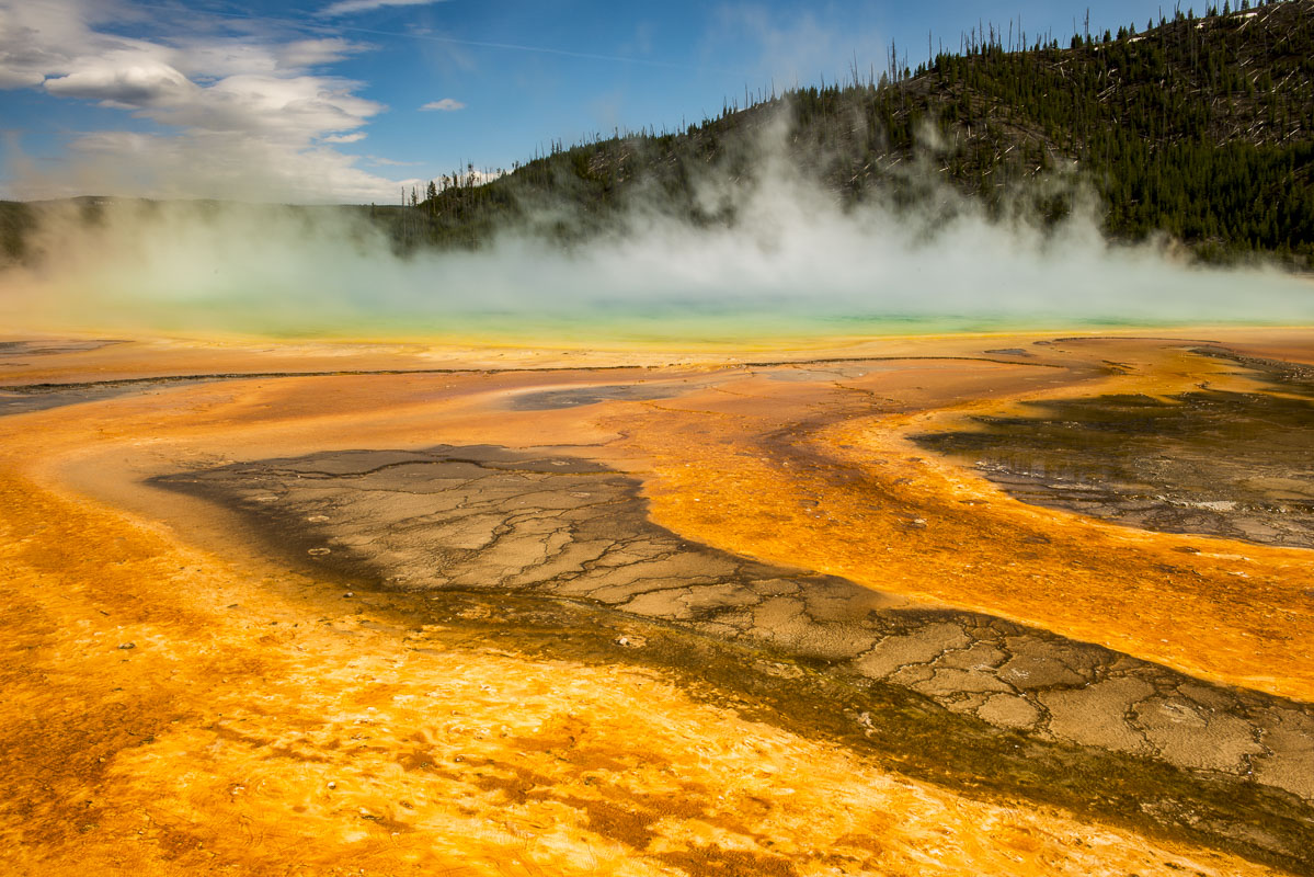 Steam rises from the Grand Prismatic Spring in Yellowstone National Park, Wyoming. The angle of the sun provides the opportunity...