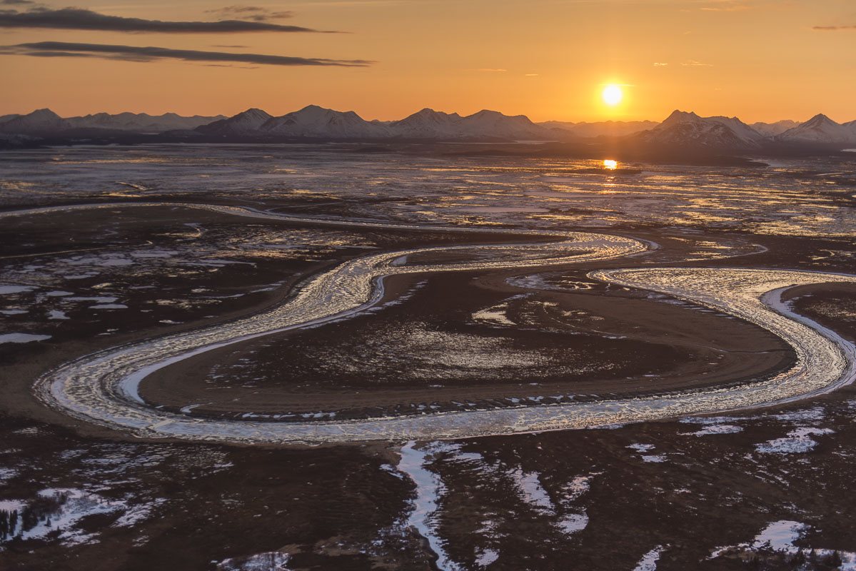 The sun sets behind the Wood River Mountains in early May, while a partially-frozen Snake River winds its way through the Togiak...