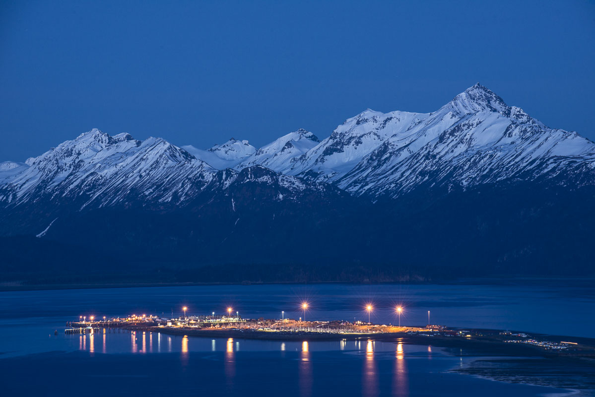 Lights from the Homer Spit add a pop of warmth against the deep blue of twilight in late spring at Homer, Alaska.
