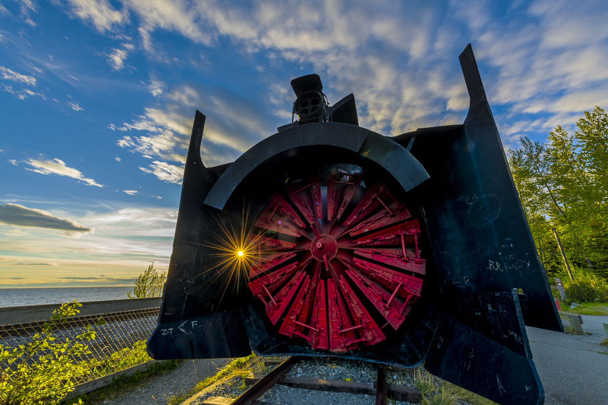 The sun shines through a tiny hole in the front of a rotary snow plow used by the railroad.