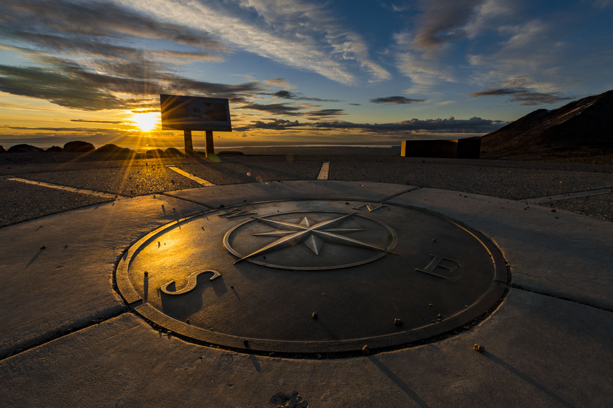 The sun sets behind the nautical compass at the Glen Alps overlook in early summer.