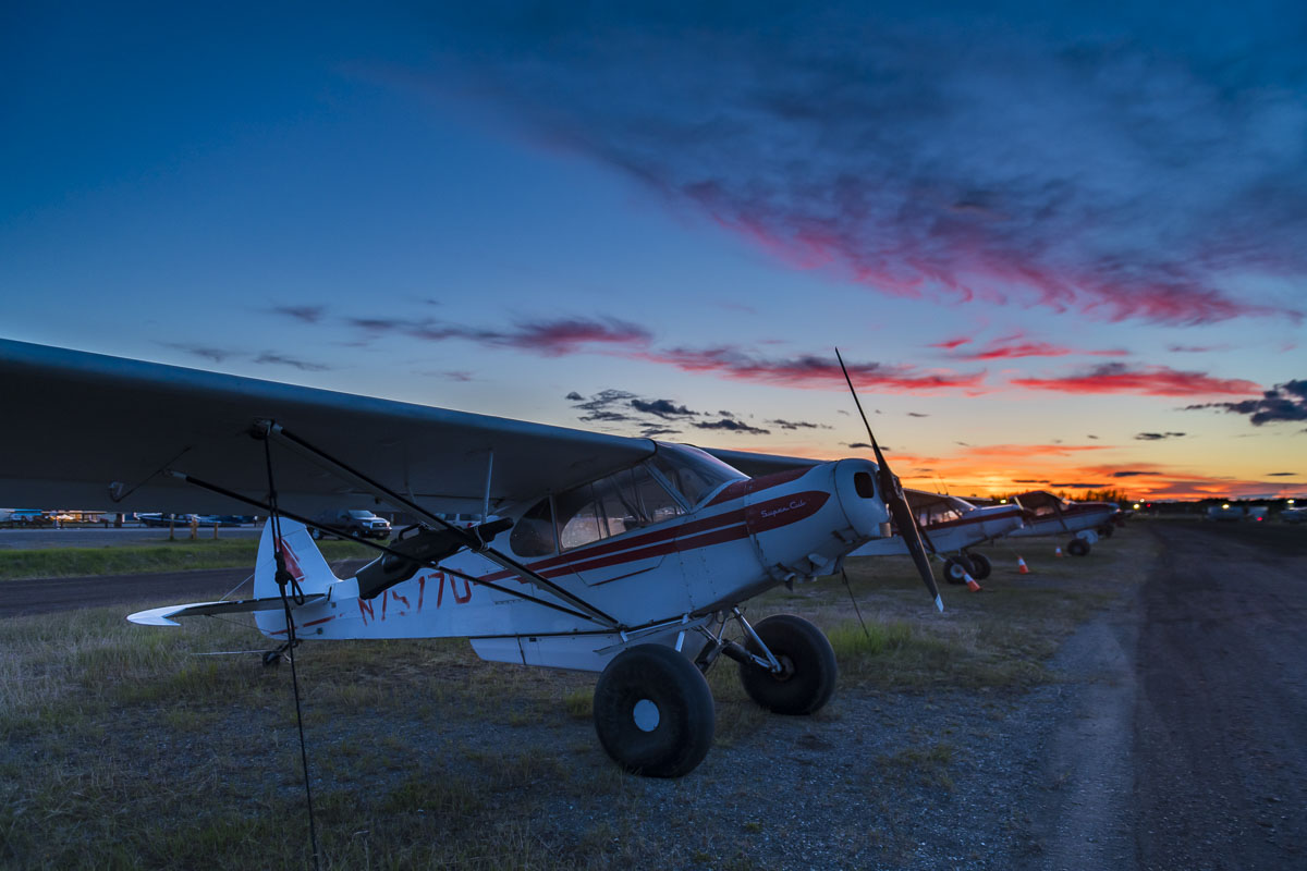 A row of small planes line a gravel runway near the Lake Hood Seaplane Base, with sunset colors lingering at 11:30 p.m.