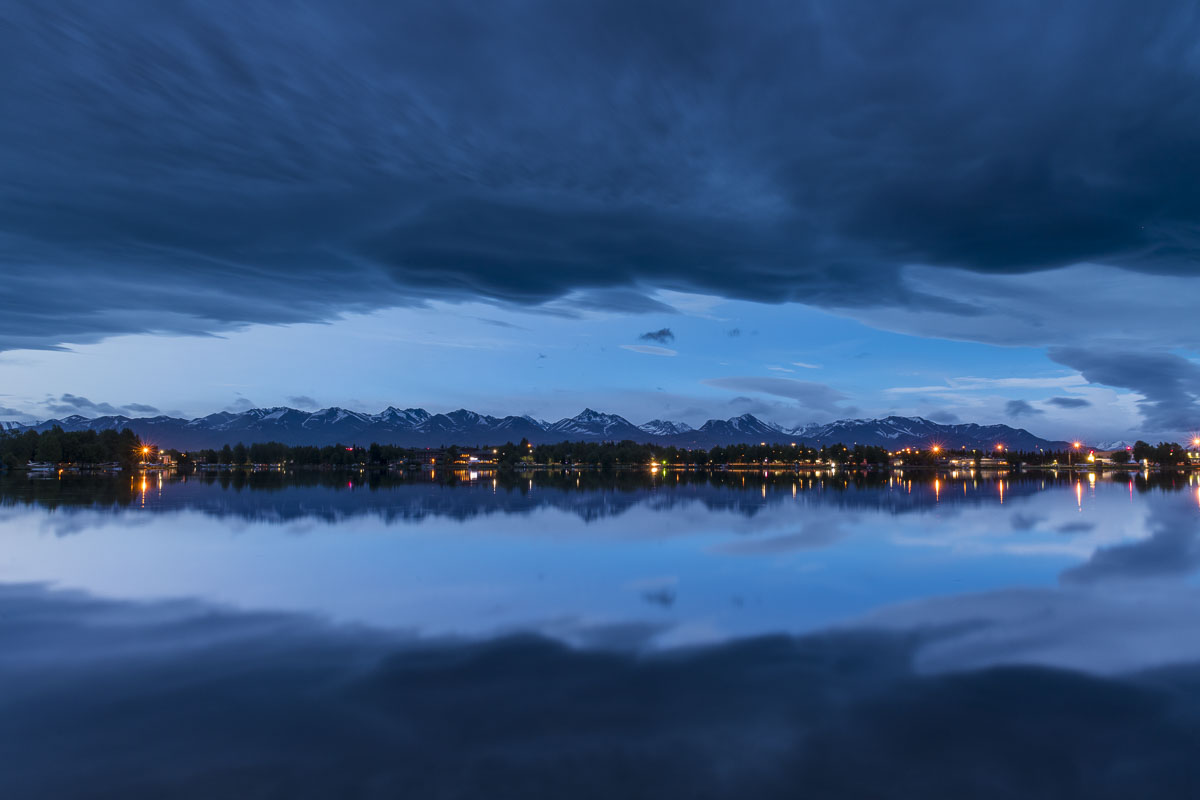 Dark clouds from a summer storm loom over Lake Spenard in Anchorage after midnight.
