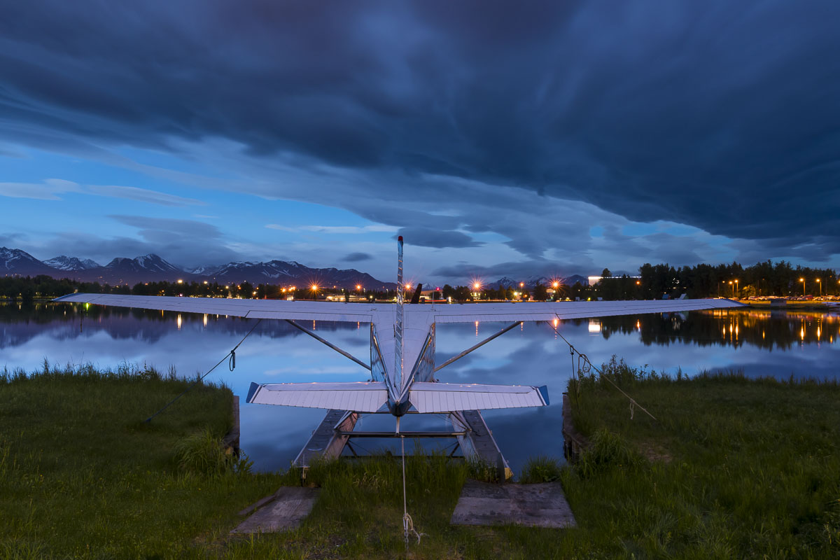 A summer storm fills the sky with dark clouds over a float plane at the Lake Hood Seaplane Base in Anchorage.