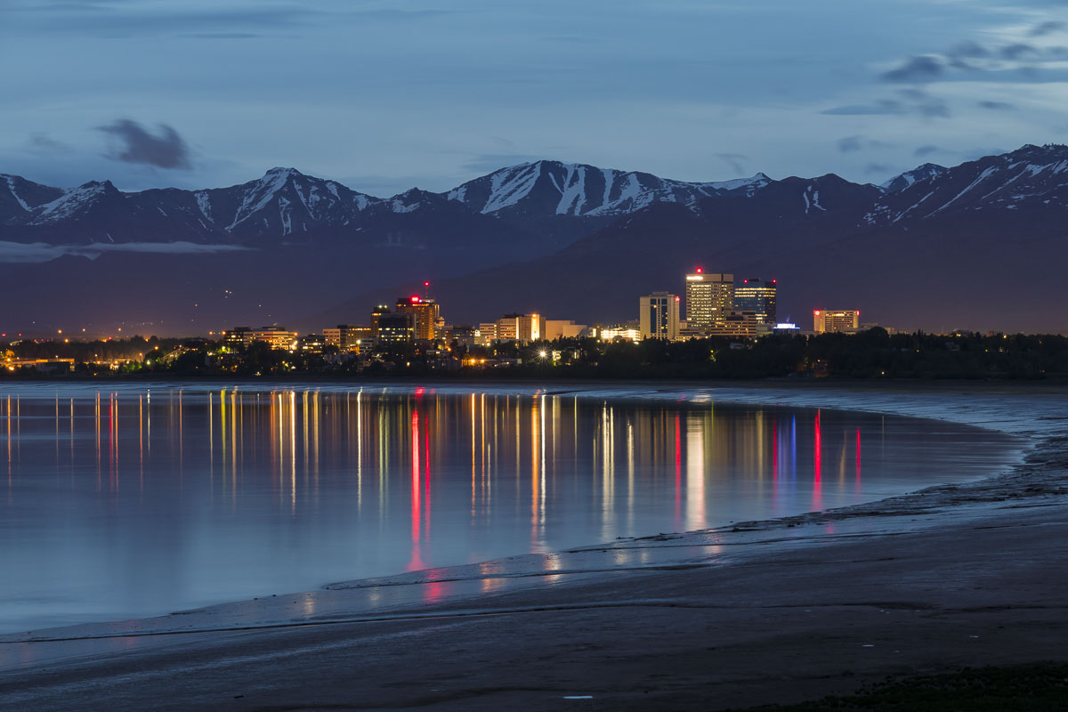 Long reflections of lights from the Anchorage downtown skyline add a rich pop of color to a cloudy summer evening.