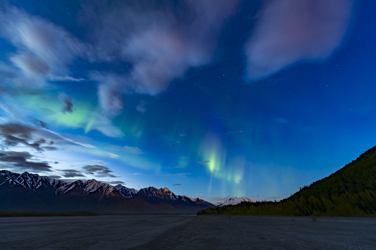 A mid-May Kp7 aurora borealis shines through the twilight over the Knik River.