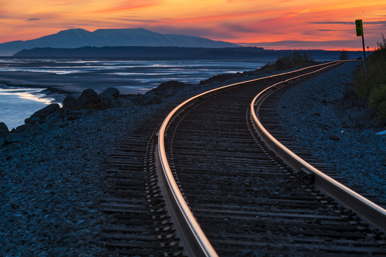Rails of the Alaska Railroad captures hues of gold to red from the colors of sunset, with Mt. Susitna (aka Sleeping Lady) stands...